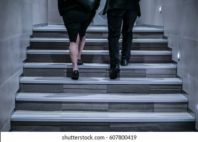 Business people are walking up the stairs.