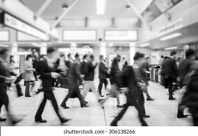 business people walking in the subway station. motion blurred black and white filter