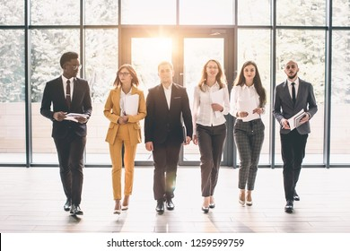 Business People Walking Toward Camera. Full length of group of happy young business people in formal wear having work meeting in modern office with large window