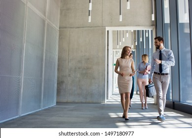Business people walking while talking in office hall