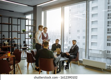 business people wearing formal wear gathered in office for holding business conference with partners, successful young guys together in modern boardroom