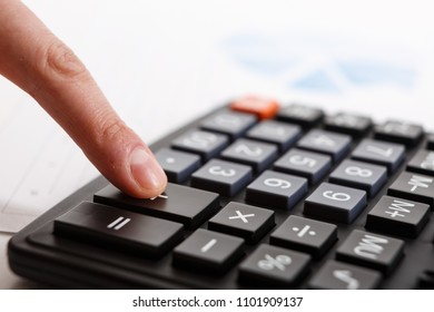 Business people who use a calculator with financial concepts