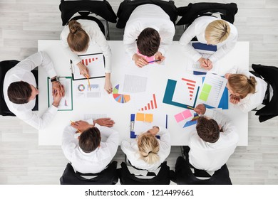 Business people work with statistics documents with tables and diagrams sitting around the table