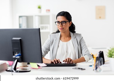 business, people, work and technology concept - happy businesswoman with computer at office