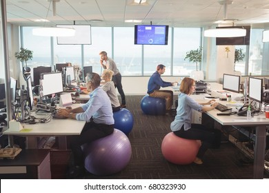 Business people working at desk while sitting on exercise balls in office