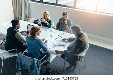 Business people working and discussing together in meeting at office. Businessman looking at building sketch with colleagues sitting around table.