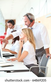 Business people working in front of computer with headphones