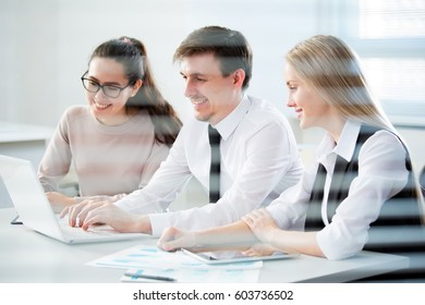 Business people working with laptop in an office. Viewpoint through the blinds