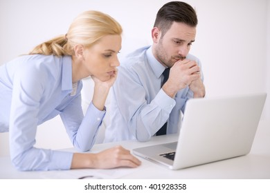 Business people working at meeting in office.They are in discussion while using a laptop.