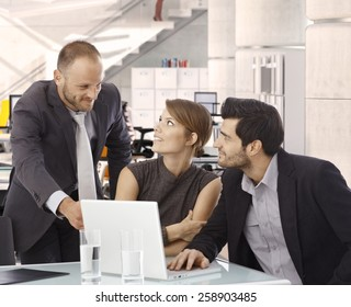 Business people working at office desk with laptop. Confident smile, pointing at screen, suit.