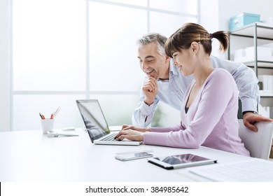 Business people working at office desk, a woman is using a laptop and her chief is watching the computer screen