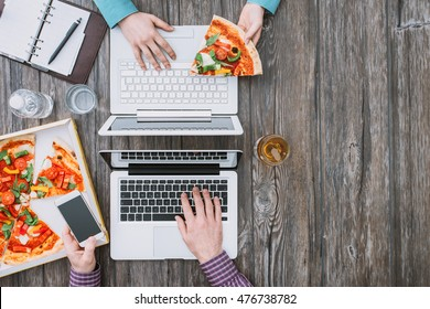 Business people working at office desk and having a lunch break with a tasty pizza, top view