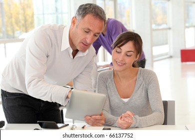 Business people working in office with electronic pad