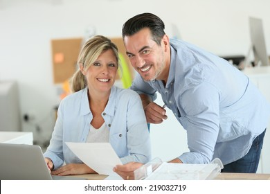 Business people working in office on laptop