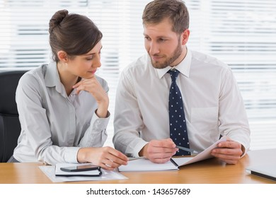 Business people working on documents together at desk in office