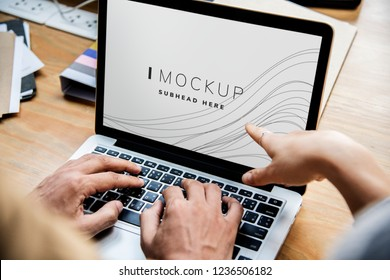 Business people working on a laptop with a screen mockup