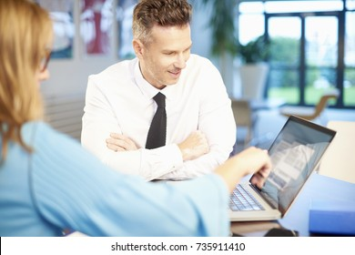 Business people working on new project. Businessman and businesswoman sitting at desk while consulting about business. Professional woman pointing something on laptop screen