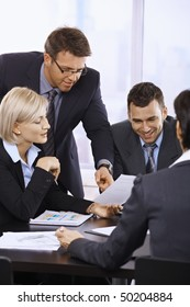Business people working together at meeting table in office.