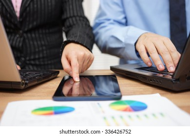 business people are working together on financial project using laptop and  tablet computer