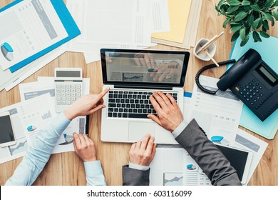 Business people working together, they are using a laptop and pointing at the screen, finance and accounting concept, top view