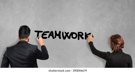 Business people writing the word Teamwork on the screen