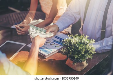 Business peoples meeting and passing money for new business project on table. investment concept