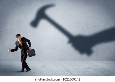 Business person afraid of a shadow hand holding hammer concept on background