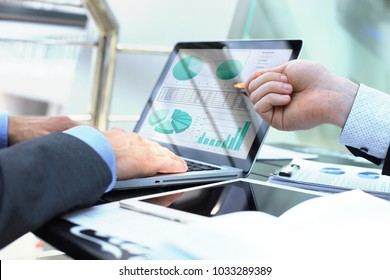 Business person analyzing financial statistics displayed on the laptop screen.