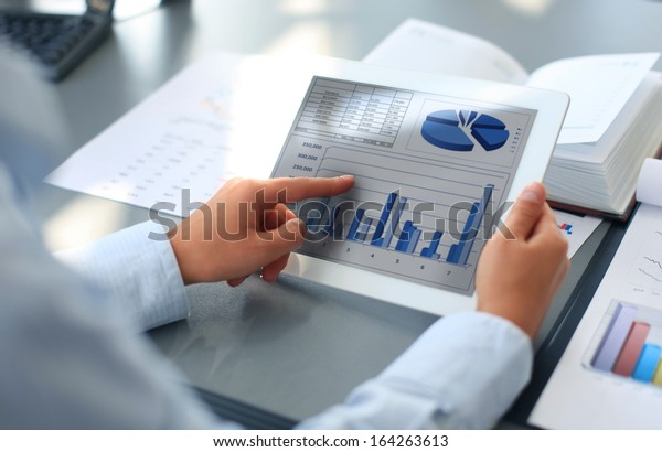 Persona de negocios que analiza las estadísticas financieras mostradas en la pantalla de tableta