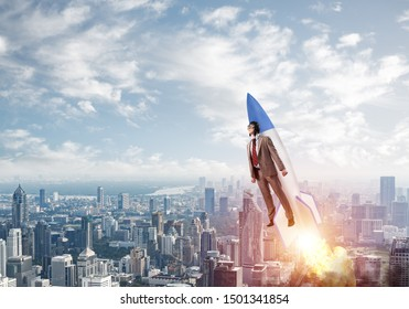 Business person in aviator hat flying on rocket. Progress and innovation technology. Corporate businessman flying with jetpack rocket in blue sky above modern city. Leadership motivation concept.