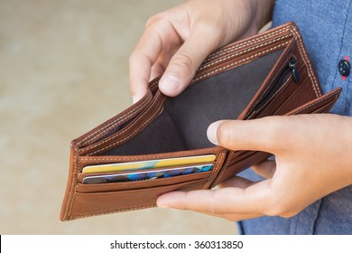 business person holding an empty wallet (no money)