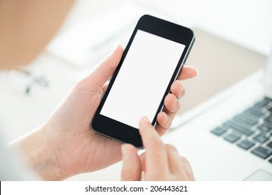 Business person holding modern smartphone and touching on a blank screen. Stylish modern office workplace on a background.
