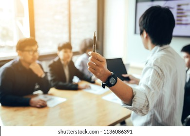 Business person holding pen and discussion with staff meeting in boardroom.