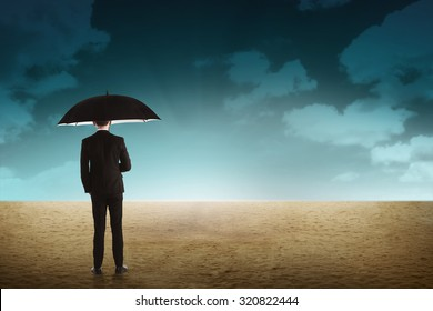 Business person holding umbrella standing on the desert