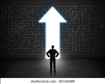 Business person looking at maze with solution arrow on the wall concept