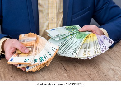 Business person placing euro banknotes into fan