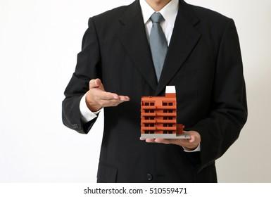 business person points apartment building miniature model
