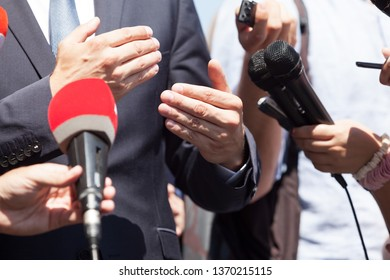 Business person or politician gesturing during press conference