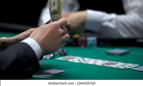 Business person pulling money out of wallet, risky poker game, bluff gambling