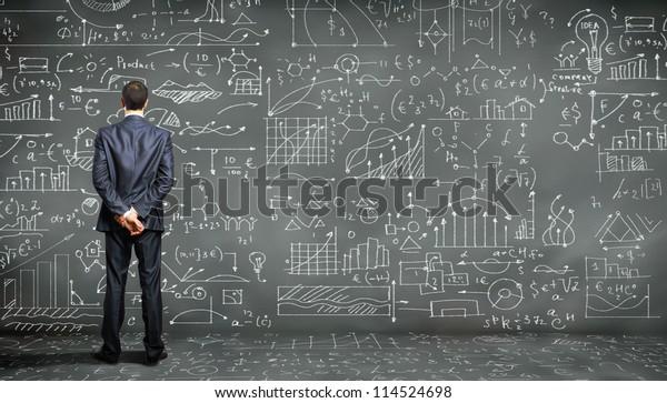 Una persona de negocios se enfrenta a la pizarra con muchos datos escritos en ella