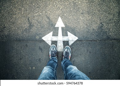 Business person standing at a crossroads. Conceptual business decision background. Point of view perspective used.