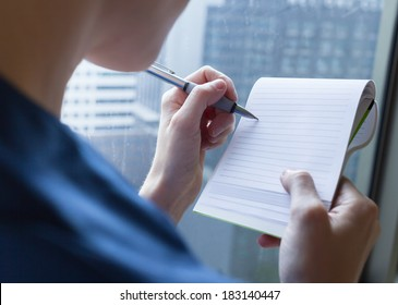 Business person taking notes during the meeting.