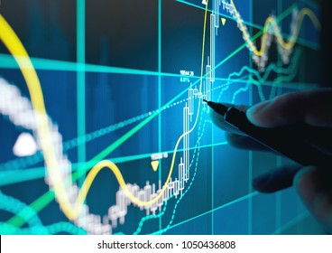 A business person tracking the technical movement of a stock chart on a computer screen.