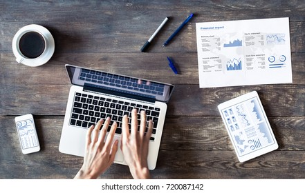 Business person working with financial report and charts on a wooden table