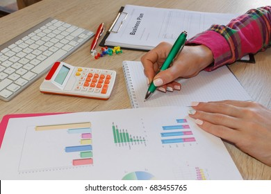 Business plan, calculator, dollar banknote on the table. Savings, finances, economy, Business and home concept - Female with calculator counting money and making notes at home
