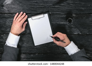 Business plan or contract template. Questionnaire form template. Blank white paper page on  with a copy space, businessman hands, quill pen and inkwell on black background.