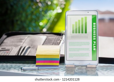 Business plan presentation on a mobile device, phone or tablet with colorful notes, binder, and pen in outdoor meeting.