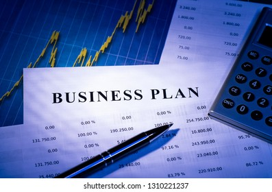 Business plan with tables, chart, a calculator and pen.