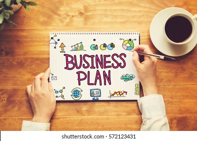 Business Plan text with a person holding a pen on a wooden desk