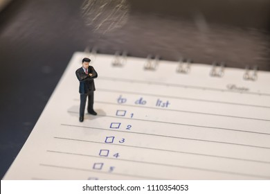 Business and planning concept. Businessman miniature figure standing on notebook with hand writing to do list.